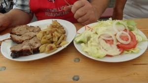 Das Essen auf dem Tisch. Rollbraten, Bratkartoffeln und Salat)